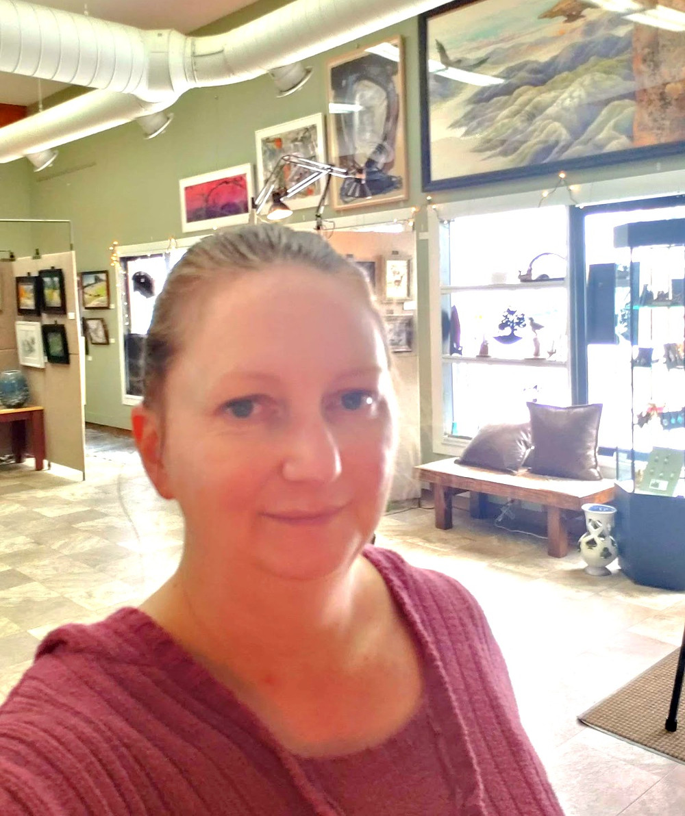 Wanda, wearing a pink sweater smiles for a selfie inside her frame shop.