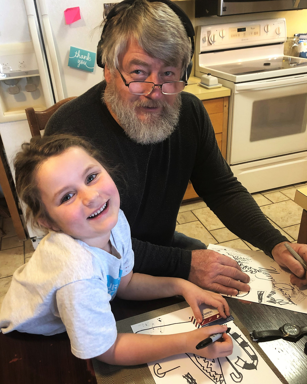 A little girl and her uncle smile at the camera while working on a drawing