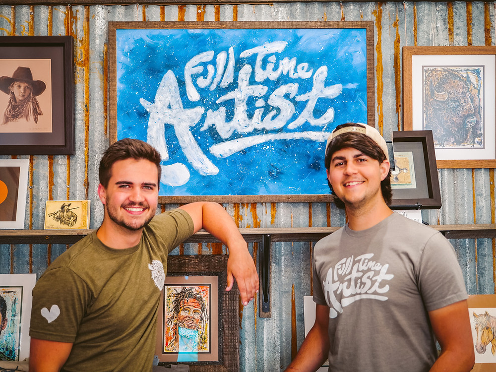 "Nathan and Micah smile for the camera in front of a sign that says ""Full Time Artist""."