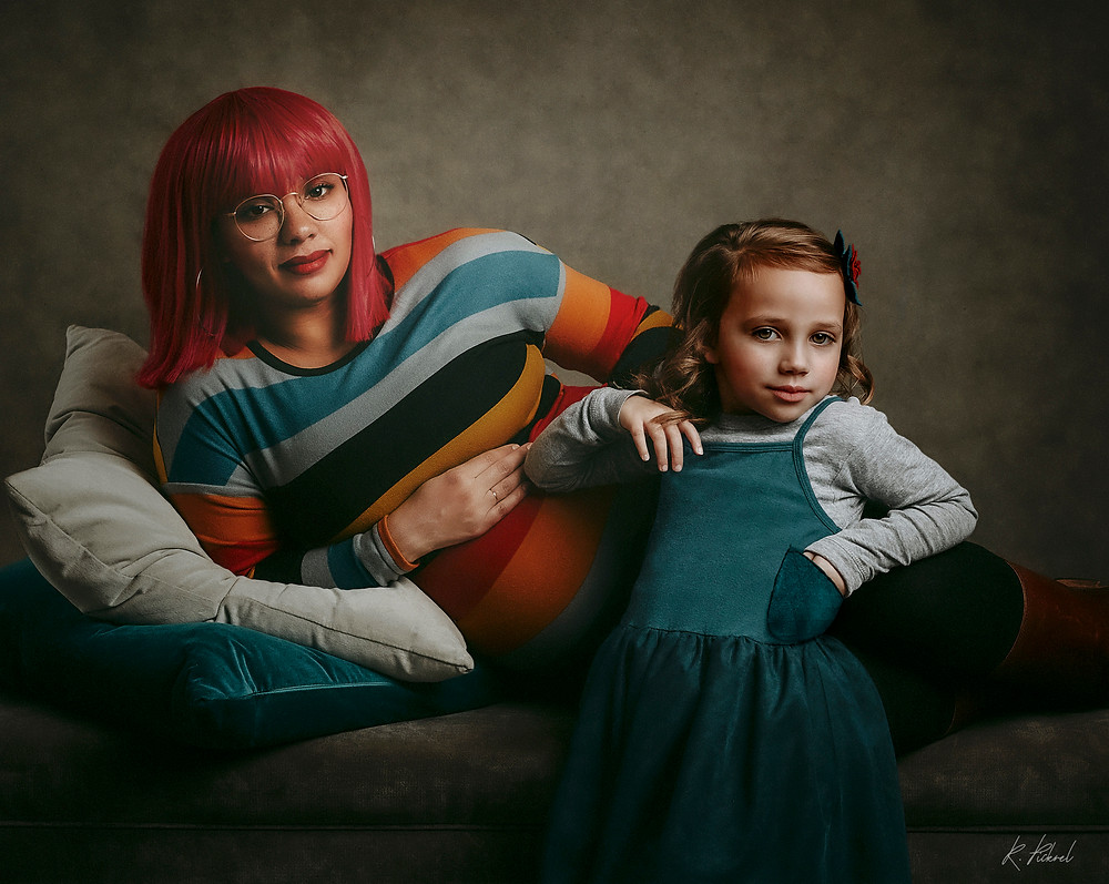 A pregnant woman with a bright red wig lounges on a couch, holding her belly and smiling at the camera. She is wearing a striped dress with bold colors. In the foreground, a little girl with ribbons in her hair poses while leaning against the woman.
