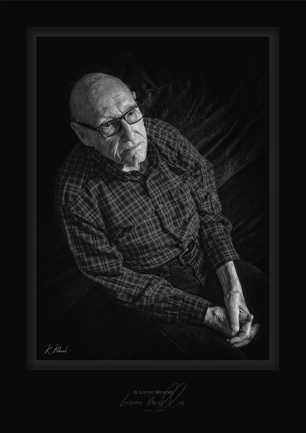 A black and white photo of an elderly man. The camera is slightly above him. His hands are folded in his lap and he looks off into the distance.