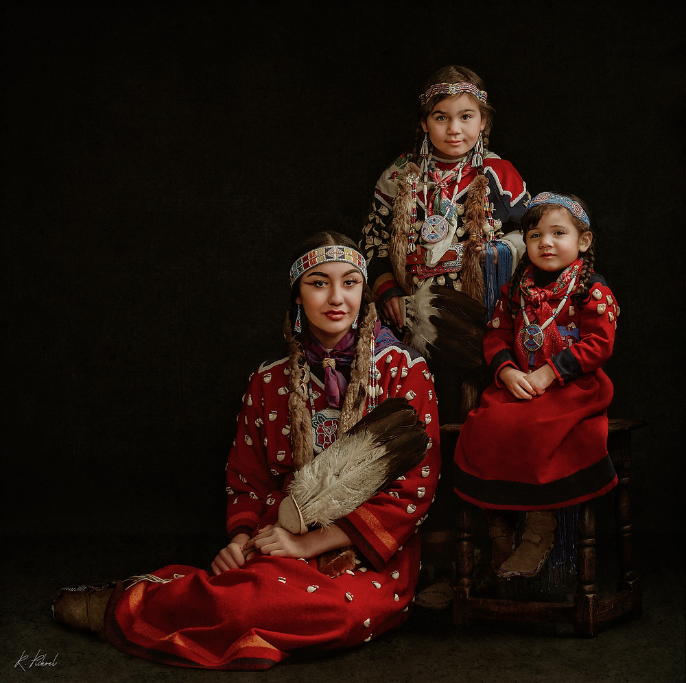 A woman, a young girl, and a toddler pose for the camera wearing traditional tribal regalia. Their dresses are red and feature elk teeth and detailed beadwork.