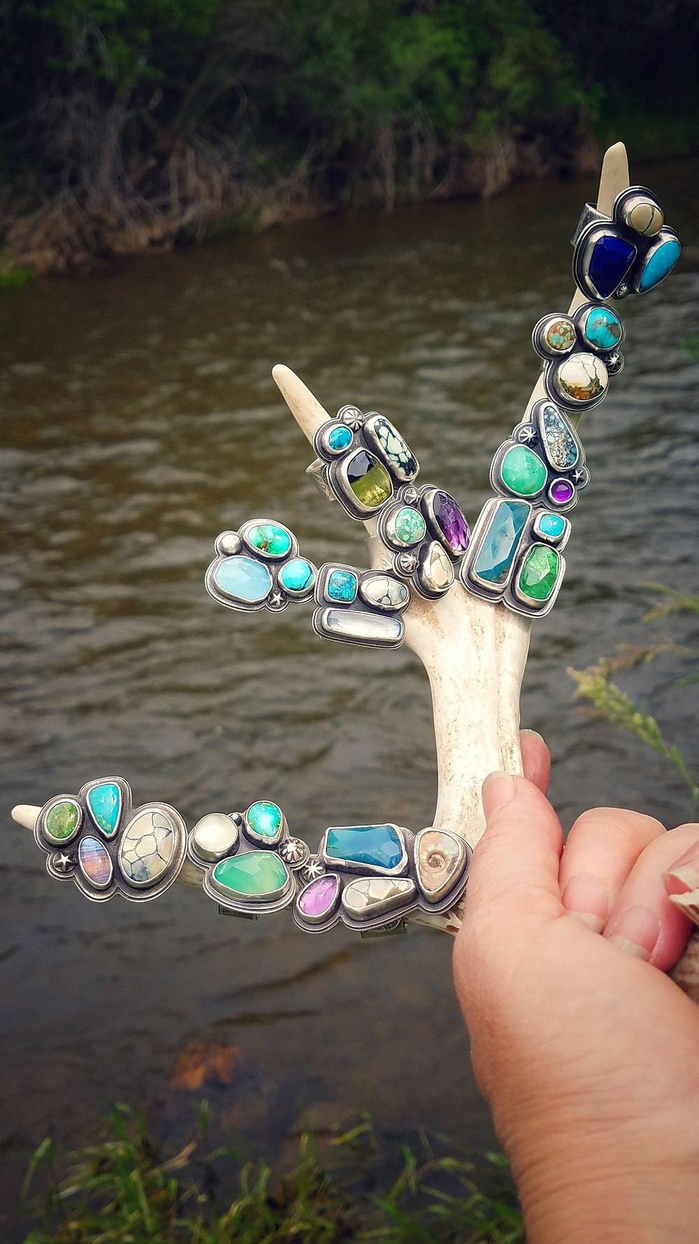 Deryn holds up a deer antler to the camera. On the prongs of the deer antler are 11 silver rings with precious stones in turquoise, blue, green, purple, white, and even a fossilized shell