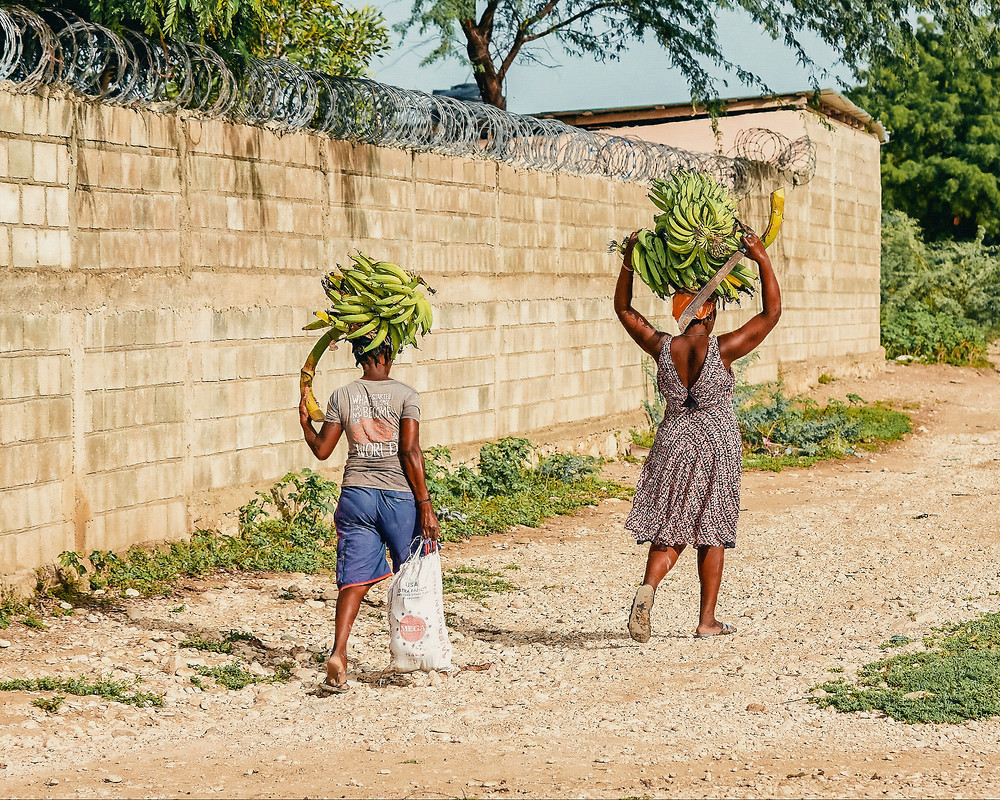 A woman and child walk away from the camera with great bushels of bananas on their heads. In the background is a tall stone wall with barbed wire wrapped on the top.