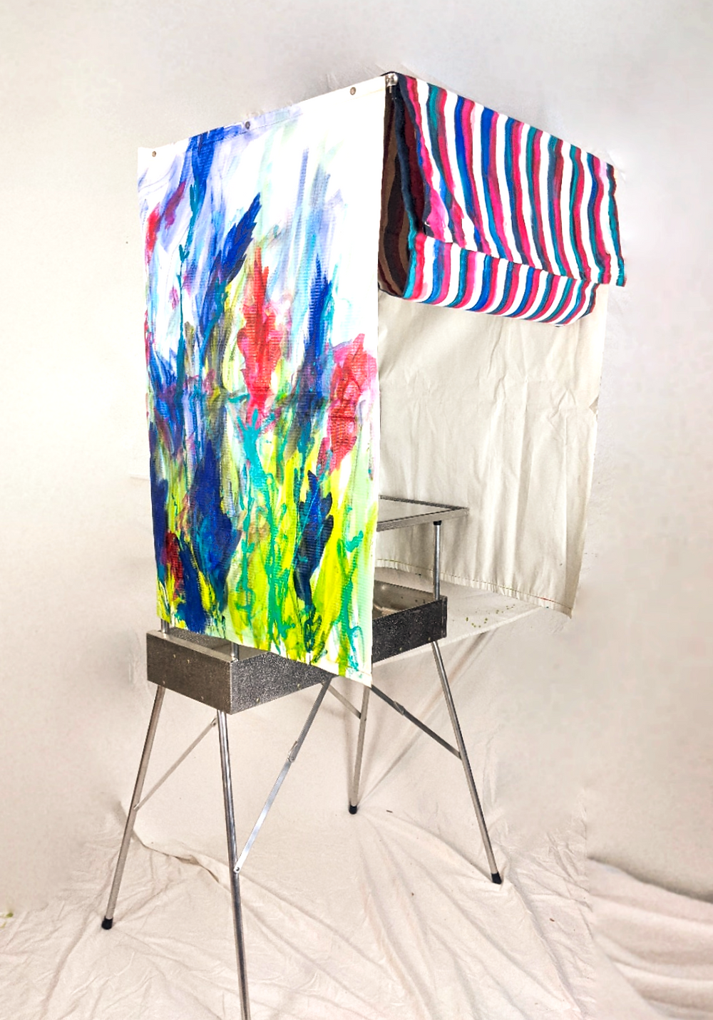 An antique voting booth with red, white, and blue striped curtains and abstract flowers painted on the sides.
