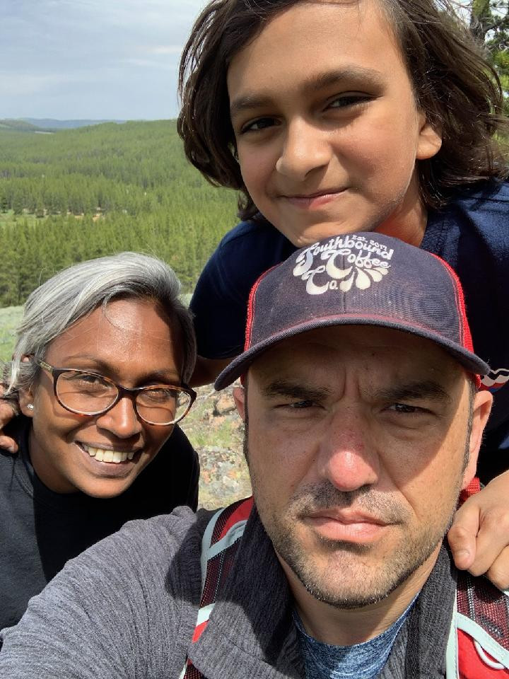 Rachel smiles at the camera, and her son Prakash rests his head on top of Ryan's head. Ryan is squinting as he takes the selfie because the sun is in his eyes. In the background there is a forest of evergreen trees in the distance.