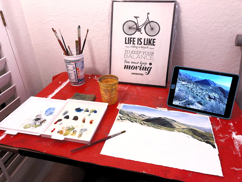 the artist's workspace, including a cup of brushes, a palette of paint, and an iPad with reference photo.