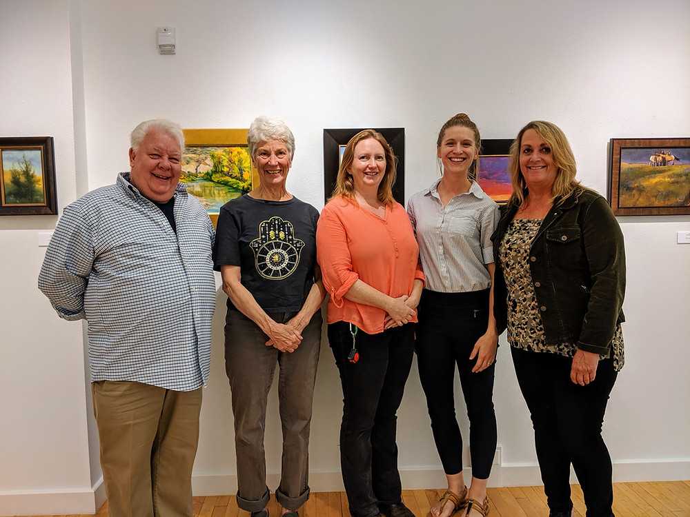 Five people stand in art gallery smiling