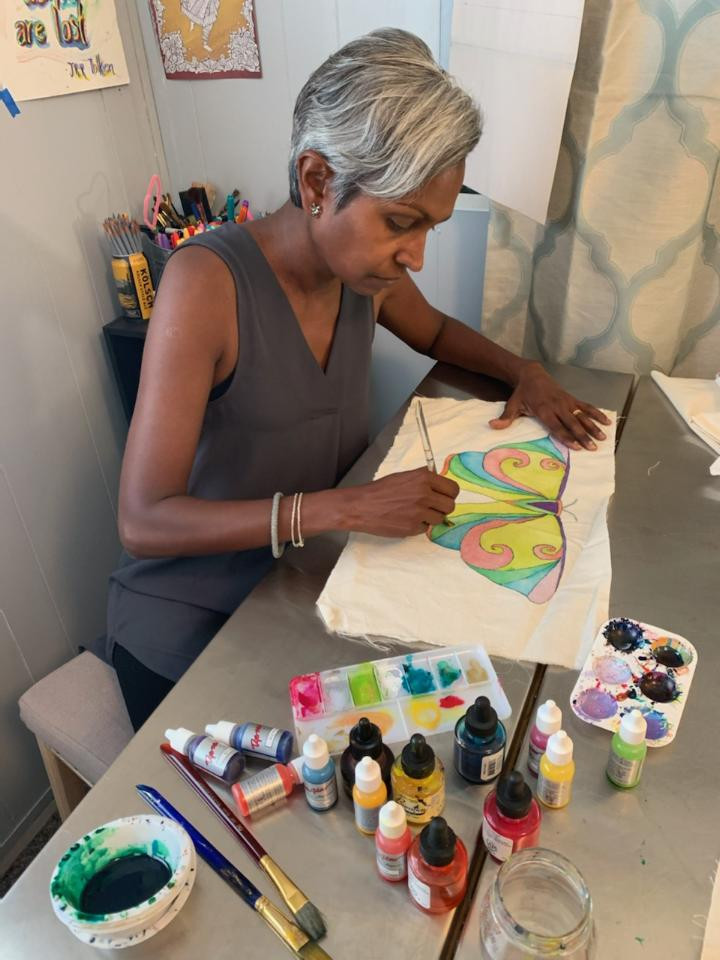 Rachel sits at her art table with brushes, inks, paint, and a palette. She is painting a butterfly on a piece of cotton fabric.