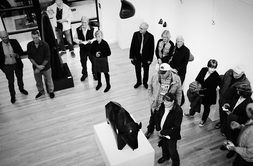 people stand in a gallery looking at sculptures