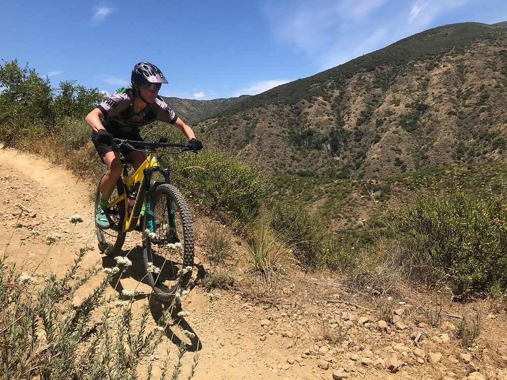 Brooke rides down a rocky trail on her yellow mountain bike.