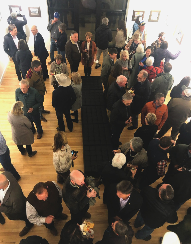 Crowd of people enjoy reception in fine arts gallery