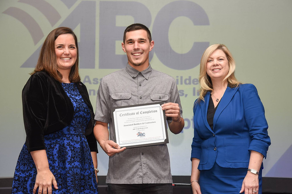 The 2018 Graduate of the Year, Joshua Stuart, Electrical Apprentice, Bergelectric (center) with President and CEO Shandon Harbour (left) and DIrector of Education Tracey Barrett (right).