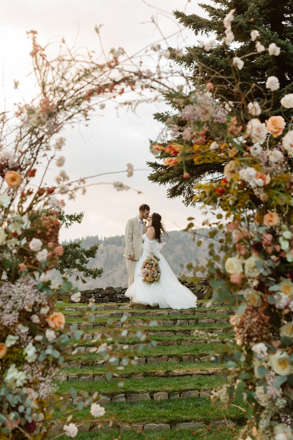 A full and organic-looking floral arch, made with spring time pinks and lush greens. A couple, male in tan tux and female in a flowy white tulle wedding dress, kiss in the distance through the arch.