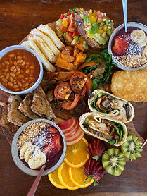 Vegan breakfast platter including acai bowl, breakfast wrap, fresh frut, bruschetta, baked beans, hash browns and fresh fruit.