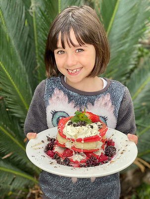Young girl holding a pancake stack, layered with fresh frut, ice cream and maple syrup