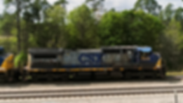 CSX train to be loaded with white poles