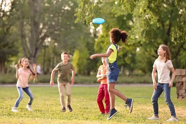 kids-throwing-frisbee-while-camping.webp