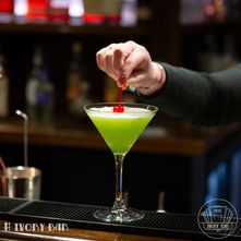 Melonie Green. Flamboyant Flapper drink of the 20s: Ivory infused kiwifruit Vodka, Melon liqueur. Pineapple overlays with cherry underlays. A showcase of visual and taste razzmatazz. One of our most popular.