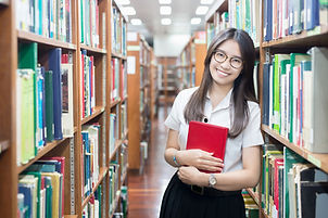 Asian student in uniform reading in the