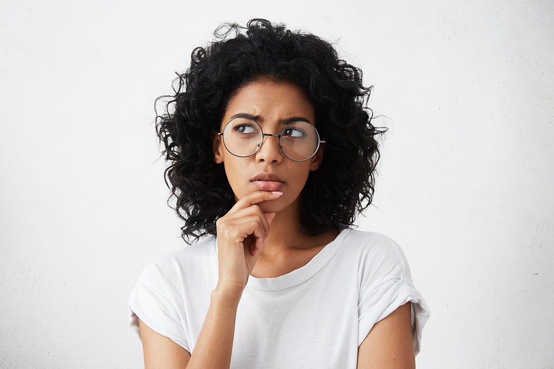 Isolated portrait of stylish young mixed race woman with dark shaggy hair touching her chi