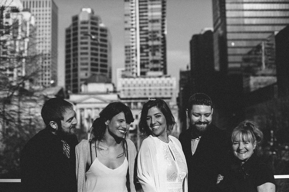 A group photo of the newlyweds and their family and friends in front of Vancouver's cityscape.