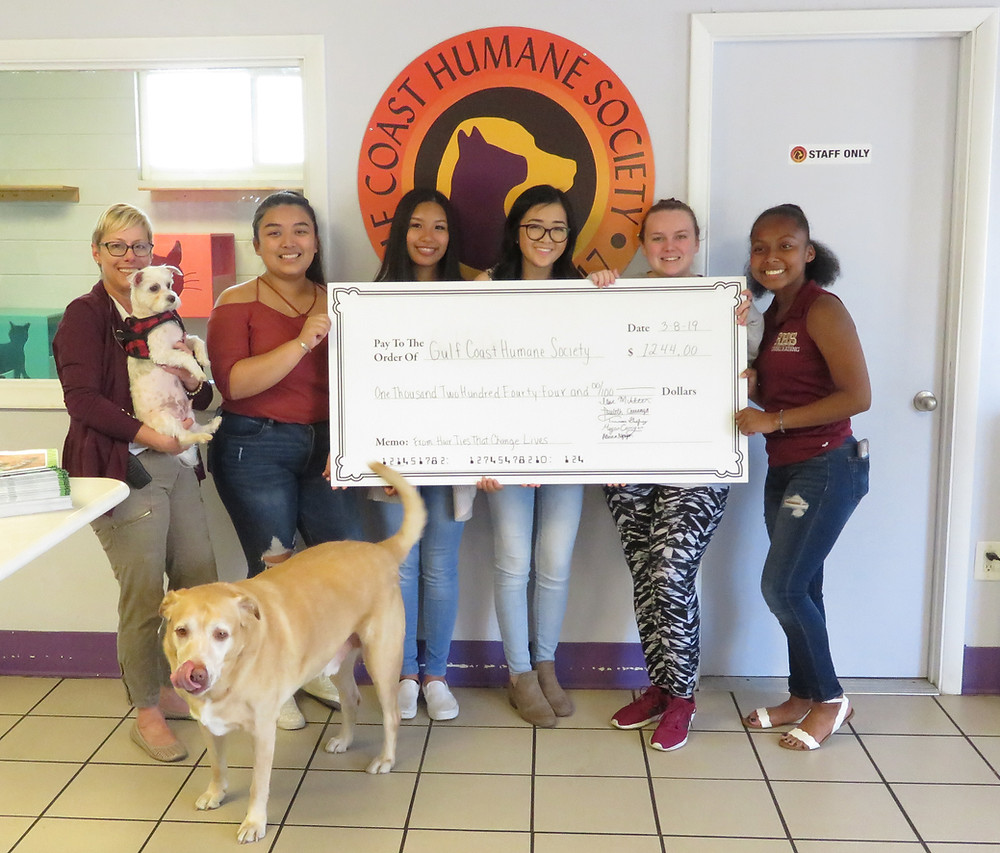 HHTCL giving check to Gulf Coast Humane Society