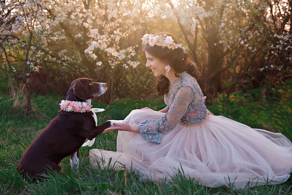 Na fotke sú dievča Simonka a jej psík Britík, ktorý je ozdobený kvetinovým venčekom ako aj jeho majiteĺka, Britík podáva labku svojej páničke, ktorá sa na neho usmieva, má hnedé vlasy, romantický účes, veĺkú tyllovú sukňu z dielne Peter a Lucia, doplnky sú od Magaela accessories, v pozadí kvitnú stromy a presvitá zlatisté slniečko v zlatej hodinke