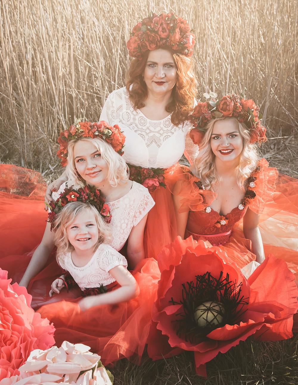 Rodinná fotografia s mamou a jej tromi dcérami, mama má ryšavé vlasy a dcéry sú blond, najmenšia má len 5 rokov, najstaršia cca 24, všetky sa krásne usmievajú, na hlave majú červené kvetinové doplnky a sedia v tráve, okolo nich sú rozloźené veľké nadrozmerné kvety z dielne Eternalflowers