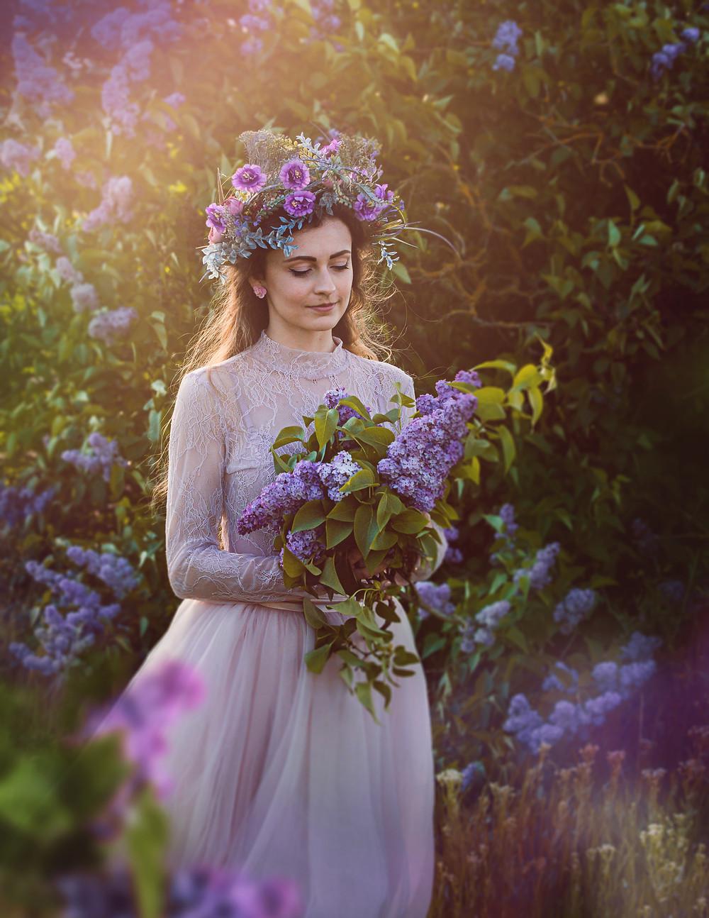 Dievča menom Terezka hľadiace na kyticu orgovánu pri zlatej hodinke, oblečená v ružovej tyllovej sukne, jemnom krajkovom bodyčku, na hlave mám veĺký fialový venček z dielne Magaela a malé ružové náušničky v tvare kvetiniek.