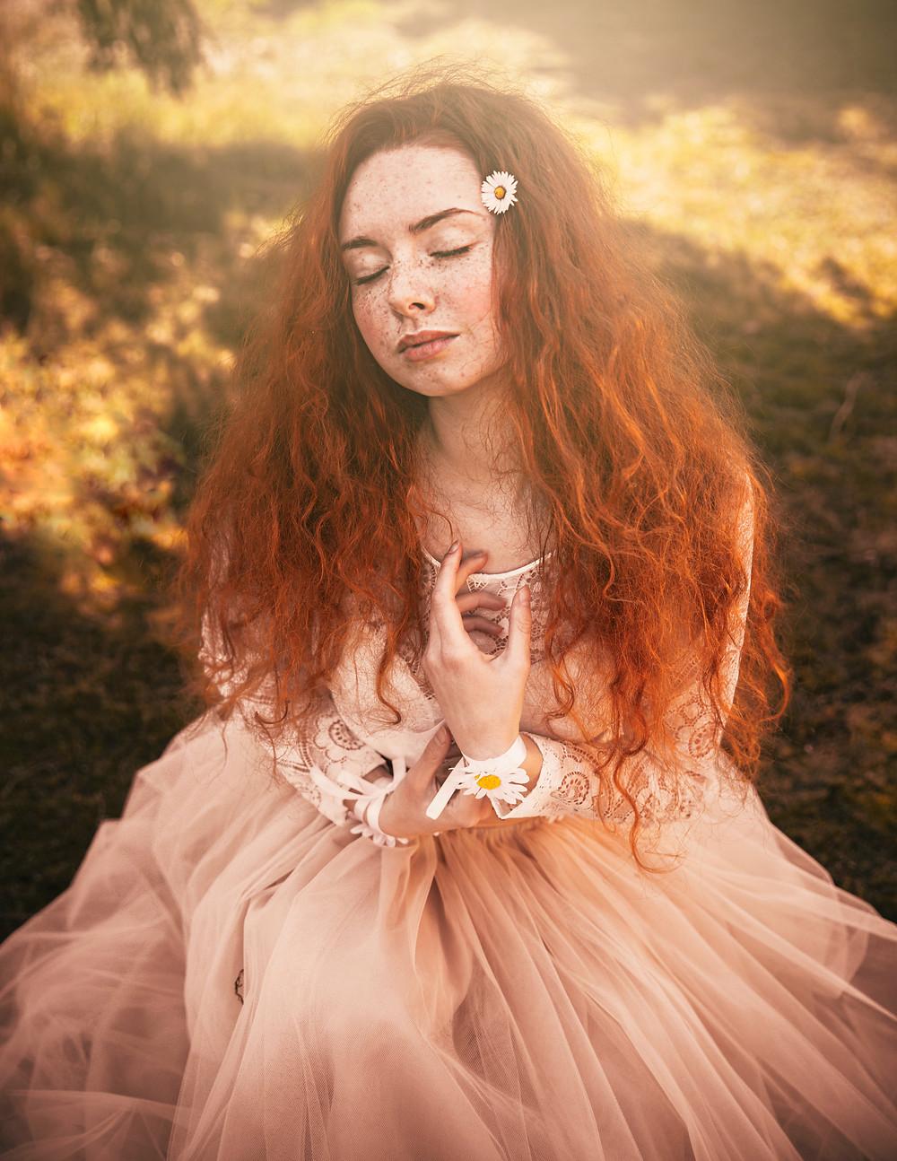 V tráve čupiace nežné ryšavé dievča zo zavretými očami, pehaté, vo vlasoch má jednú margarétku, fotografia je celá zlatistá, oblečenú má veĺľkú, prírodnú tyllovú sukňu béźovej farby a oblečené biele krajkové body s dlhým rukávom, v pozadí je zelená tráva a na rukách má náramky z Margarétok