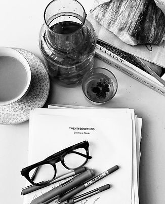"""Black and white photo of a tea, a croissant, pens, glasses, and a manuscript for """"Twentysomething"""""""