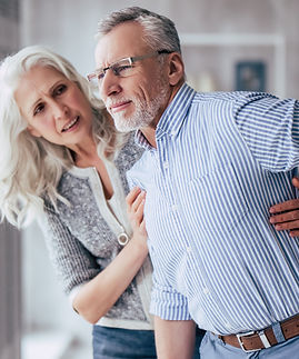 Senior couple at home. Handsome old man is having back pain and his attractive old woman s