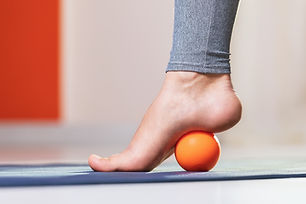 Myofascial relaxation of the muscles of the foot with a massage ball on a mat at home, clo