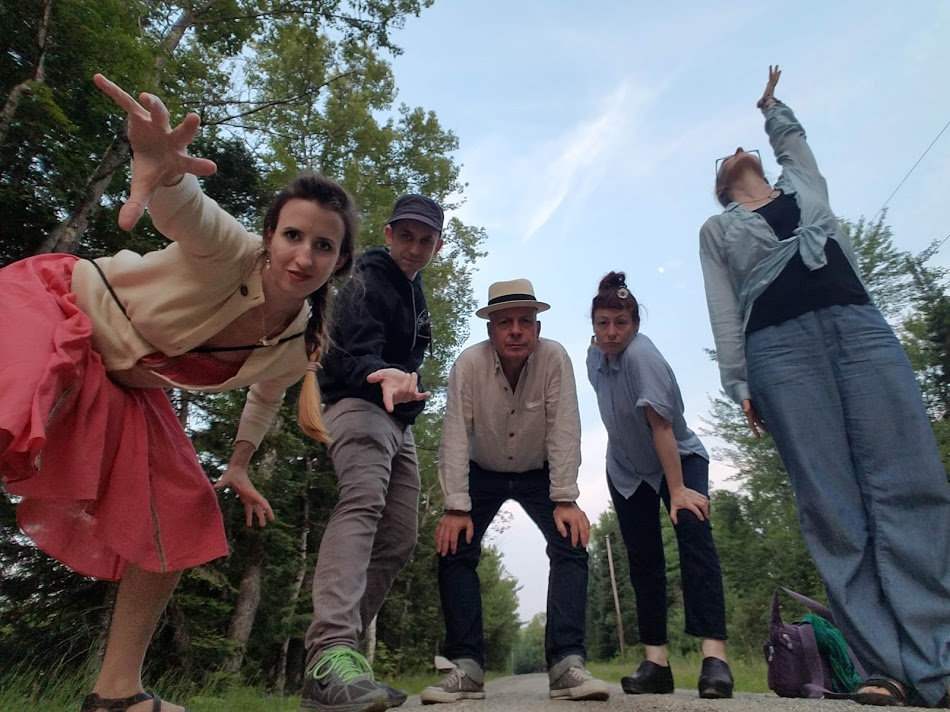 Photo of the 5 ensemble members standing above camera posing theatrically at the edge of a forest