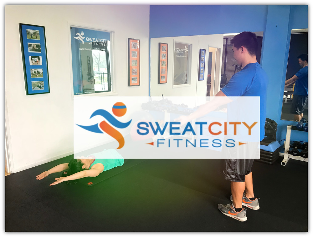 Photo of Coach Chris instructing a Client doing core work