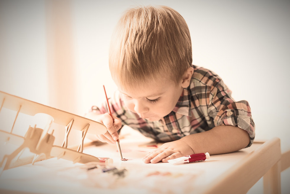 A young Child painting at a desk