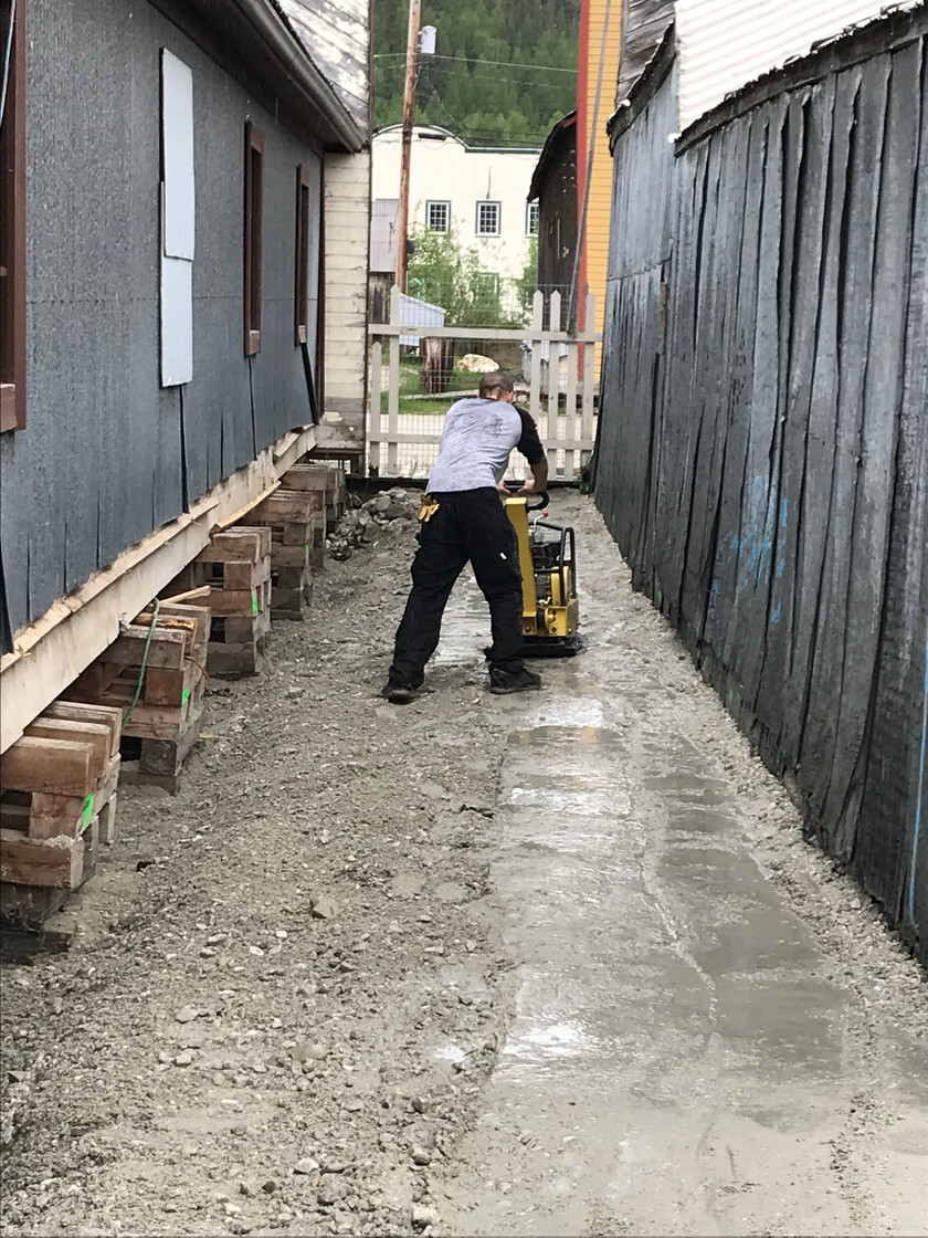 Riley compacting gravel at the side of Dawson Lodge