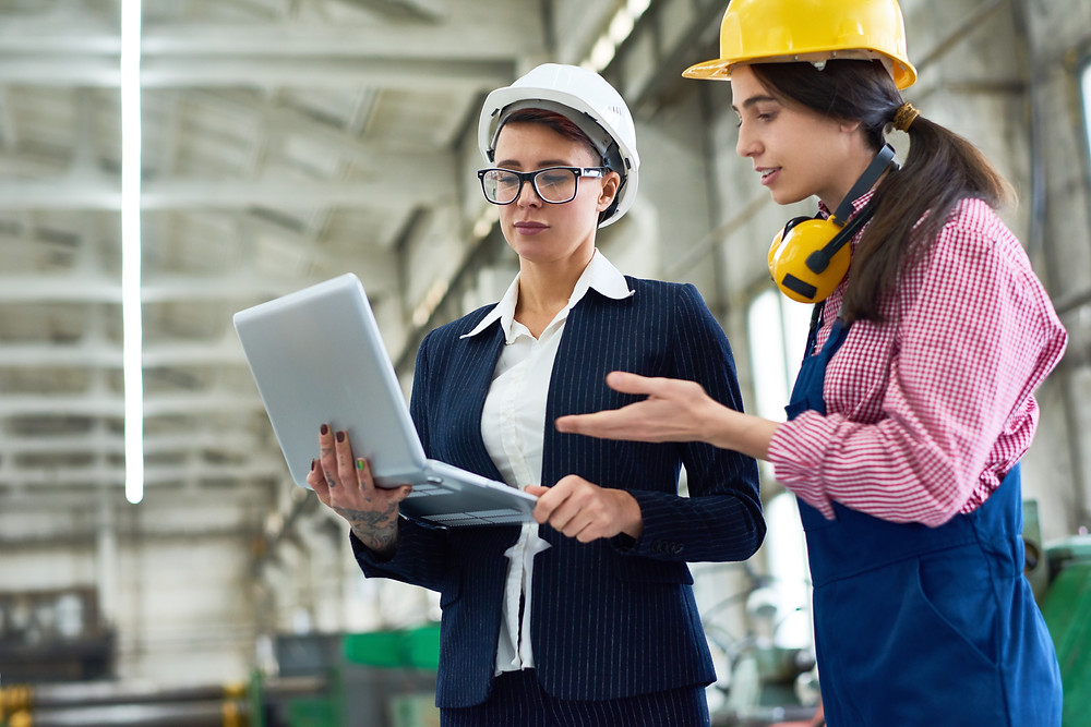 Two women in a factory wearing hard hats and using asset tracking and management system Custella