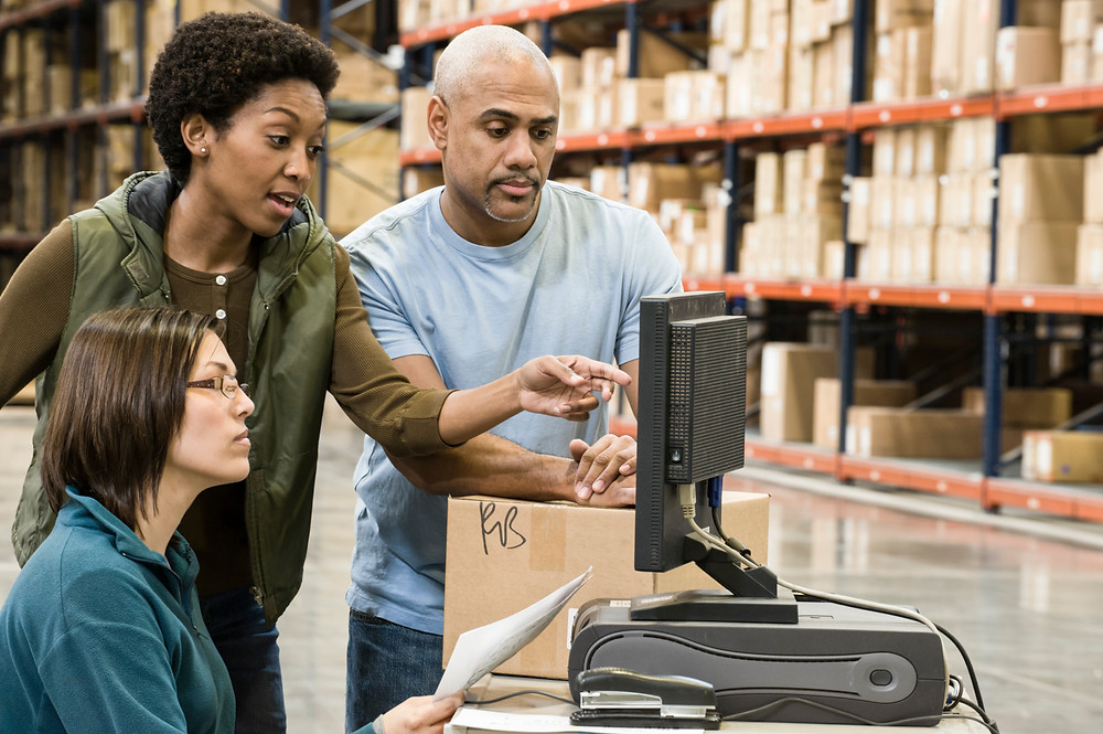 Three people in a warehouse using Custella, an asset management software system