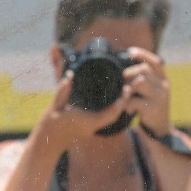 Reflexo de mulher com camêra na frente do rosto, autorretrato
