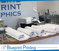 "4 rolls of white blueprints sitting on top of a table. The bottom says ""blueprint printing."""