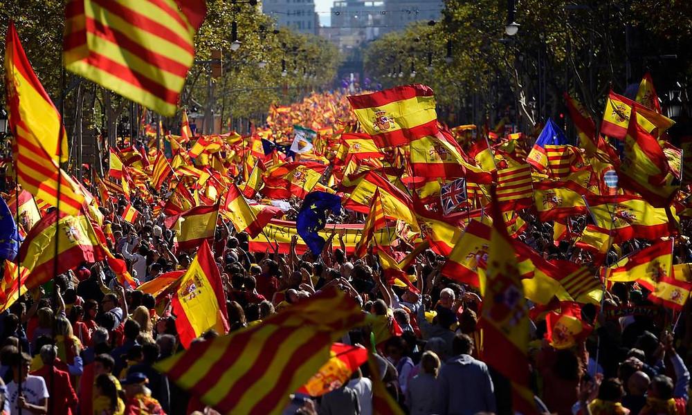Manifestantes balançam bandeiras espanholas e catalãs durante marcha a favor da unidade da Espanha em Barcelona. Mais de um milhão de pessoas se reuniram no centro da cidade para um grande protesto pacífico após Madri destituir o governo regional, em resposta à declaração unilateral de independência