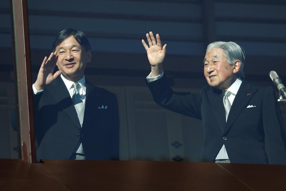 O Imperador Akihito, acompanhado do filho e herdeiro do Trono, Príncipe Naruhito, acenam para o público (Issei Kato/REUTERS)