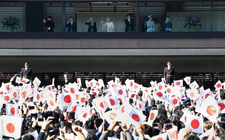 Multidão agita bandeiras do Japão durante celebração (Toru Yamanaka/AFP)