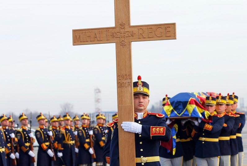 A guarda de honra carrega o caixão com os restos mortais do Rei Miguel, cruz à frente