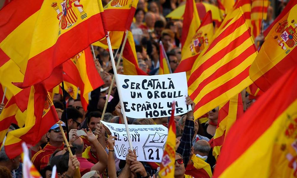 """Manifestante segura cartaz """"Ser catalão é um orgulho, ser espanhol é uma honra"""""""