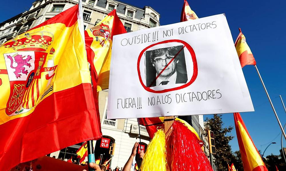 """Cartaz com imagem de líder catalão, Carles Puigdemont, diz """"Fora! Não aos ditadores"""" em manifestação a favor da unidade da Espanha. Considerada uma ofensa pelos separatistas, a intervenção de Madri na região é vista com certo alívio por cerca de metade dos 7,5 milhões de habitantes da Catalunha que, após anos eclipsados pelas mobilizações independentistas, aumentaram seus protestos"""