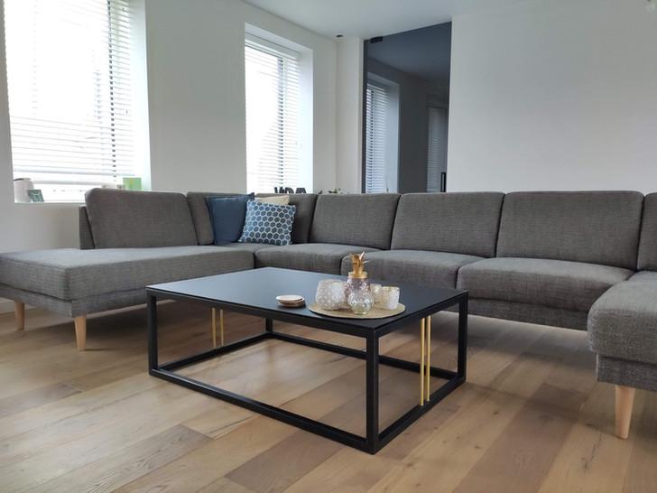 Salontafel met glazen tafelblad en grijze glazen deur tussen living en hal