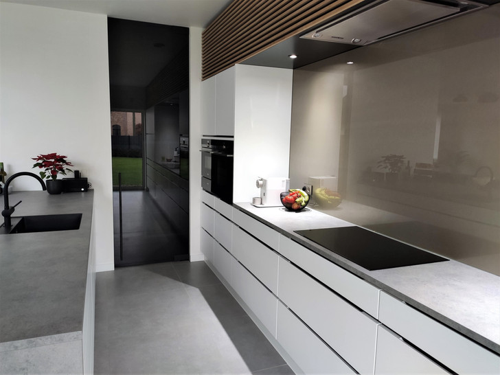 Grijze glazen deur tussen keuken en berging & spatwand in RAL 1035 (parelmoer grijs)